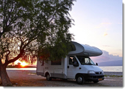 Motorhome parked besides tree - sunset